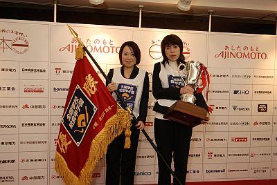 優勝旗、優勝トロフィーを手にする秋山栄養士(左)小川調理員(右) の画像