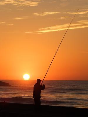 日の出の中の釣り人